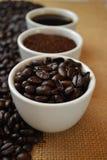 Kaffebönor, jordkaffe och svart kaffe i vita koppar Arkivbild
