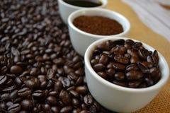 Kaffebönor, jordkaffe och svart kaffe i vita koppar Royaltyfri Fotografi