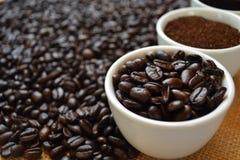 Kaffebönor, jordkaffe och svart kaffe i vita koppar Royaltyfria Foton