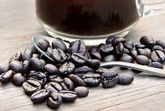 Kaffebönor, kaffesked och kopp kaffe på träbackgroun Royaltyfri Fotografi