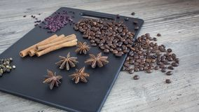 Kaffebönor, kanelbruna pinnar och stjärnaanis Kryddor och mat på trätabellen Ingredienser för framställning av kaffe royaltyfri fotografi