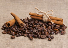 Kaffebönor, kanelbruna pinnar på säckväv Royaltyfri Fotografi