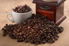 Kaffebönor, kopp och kaffekvarn Arkivbild