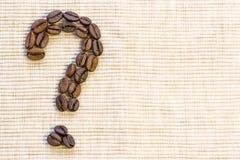 Kaffebönor läggas ut i form av en frågefläck på en vara arkivbilder