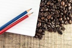Kaffebönor med anteckningsboken och blyertspennan Arkivfoton