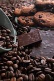 Kaffebönor med choklad och kakor i en kopp och en platta royaltyfri foto