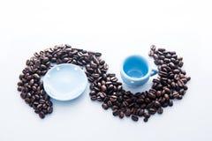 Kaffebönor med den blåa espressodishwaren Royaltyfria Bilder