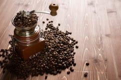 Kaffebönor med kaffekvarnen på den bruna trätabellen, kopieringsutrymme arkivfoton