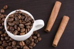 Kaffebönor med kanelbruna pinnar och koppen kaffe arkivbild