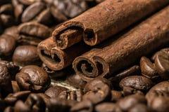 Kaffebönor med kanelbruna pinnar på säcktextilen Arkivfoton