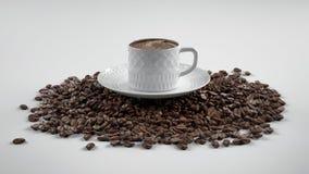 Kaffebönor med koppen Arkivfoton