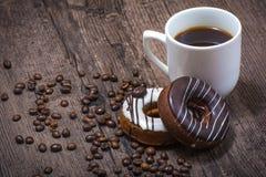 Kaffebönor med koppen kaffe och donuts arkivfoto