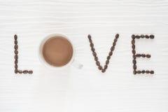 Kaffebönor med koppen kaffe på trätabellen Arkivfoton