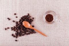 Kaffebönor och ögonblickligt kaffe i kopp Arkivfoton