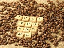 Kaffebönor och bokstäverna PRECIS DIG OCH MIG på en hessiansbakgrund Arkivfoto
