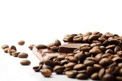 Kaffebönor och chokladstycken på vit arkivbild