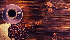 Kaffebönor och en kopp kaffe på en träbakgrund Arkivbild