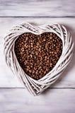 Kaffebönor och en vit hjärta Arkivbild