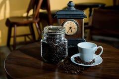 Kaffebönor och gammal klocka Arkivbild