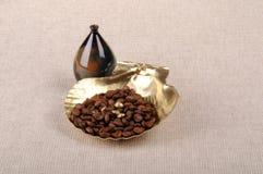 Kaffebönor och guld- skal Royaltyfri Foto