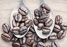 Kaffebönor och kaffesked på träbakgrund Arkivbilder