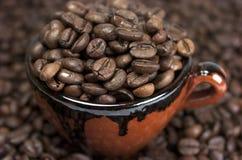 Kaffebönor och kopp arkivfoto