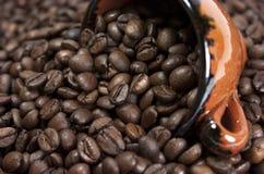 Kaffebönor och kopp royaltyfri bild