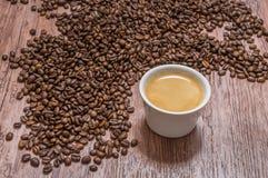 Kaffebönor och kopp av varmt kaffe Arkivbilder