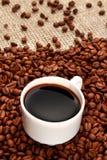 Kaffebönor och kopp kaffe på säckväv arkivbilder