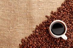Kaffebönor och kopp kaffe på säckväv royaltyfri fotografi