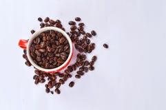 Kaffebönor och röd kopp Arkivfoto