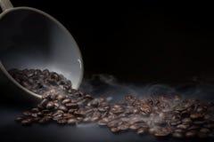 Kaffebönor och rök som tar i väg från kaffefrö royaltyfri bild