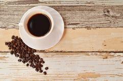 Kaffebönor och träbakgrund Arkivfoto