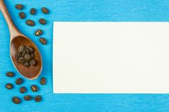 Kaffebönor och träsked på en blå bakgrund arkivfoton