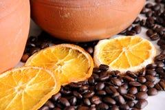 kaffebönor och tre stycken av den torkade apelsinen på tabellen på bakgrunden av leradisk arkivbild