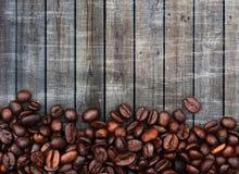 Kaffebönor och wood bakgrund arkivbilder