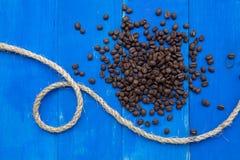 Kaffebönor på blått träbräde Arkivfoto