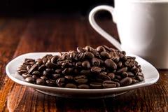 Kaffebönor på den vita plattan med kaffekoppen Fotografering för Bildbyråer