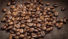 Kaffebönor på en kanfasservett, mörkt naturligt kaffe, mat, kanfas, närbild arkivbild