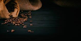 Kaffebönor på en mörk träbakgrund Arkivfoto