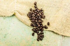 Kaffebönor på en säckvävsäck och konkreta tegelplattor Arkivbild