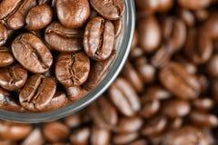 Kaffebönor på en tabell i ett exponeringsglas Royaltyfri Bild