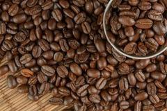 Kaffebönor på en tabell och en kopp Arkivfoto