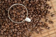 Kaffebönor på en tabell och en kopp Arkivbild