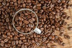 Kaffebönor på en tabell och en kopp Royaltyfria Bilder