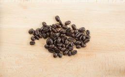 Kaffebönor på en träbakgrund Arkivbilder