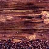 Kaffebönor på en träbakgrund Arkivfoto