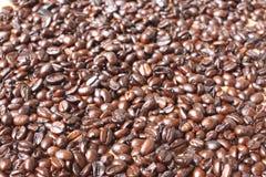 Kaffebönor på en trätabell arkivfoton