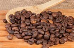 Kaffebönor på ett trägaller Arkivbild