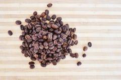 Kaffebönor på ett wood bräde Arkivbild